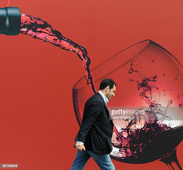 A man passes by a giant picture of red wine at the Vinitaly on April 4 2009 in Verona Italy Vinitaly the international wine and spirit exhibition...
