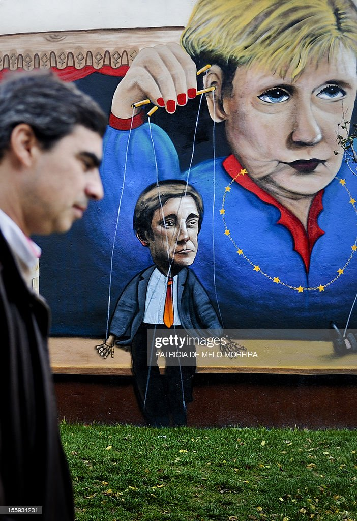 A man passes by a graffiti depecting German Chancellor Angela Merkel handling string puppets of Portuguese Prime Minister Pedro Passos Coelho (L) in Lisbon on November 9, 2012. German Chancellor Angela Merkel will visit Lisbon on November 12, 2012. AFP PHOTO / PATRICIA DE MELO MOREIRA
