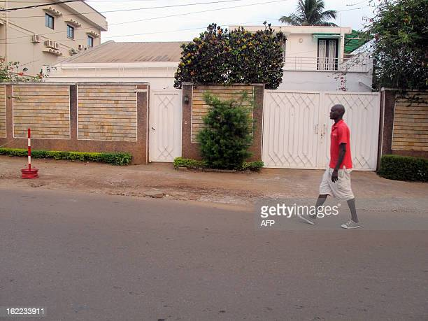 A man passes by a house on February 21 2013 in the Bastos district of the Cameroonian capital Yaounde where live seven members of a French family who...
