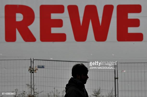 A man passes by a logo of German supermarket chain Rewe on October 14 2016 in Berlin After negociation talks between the Tengelmann group and...