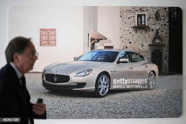 A man passes by a poster displaying a Maserati Quattroporte at a Maserati plant on May 22 2014 in Grugliasco near Turin The plant was renamed after...