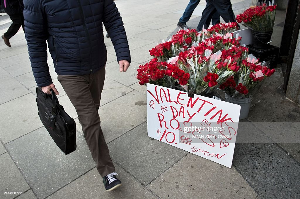 A man passes by a vender selling roses above a metro Stop on February 12, 2016 in Washington, DC. Valentine's Day is observed on February 14. / AFP / Brendan Smialowski