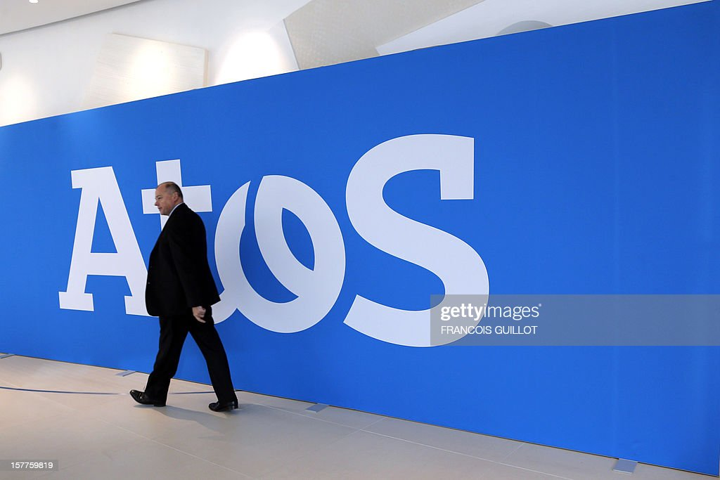 A man passes by a wall displaying a logo of the IT services company Atos, on December 6, 2012 in Bezons, north of Paris. CEO of the IT services company Atos, Thierry Breton and French industrial group Bollore's head, Vincent Bollore gave a joint press conference in Bezons to announce the launching of My Car, the first Atos electric car fleet powered by solar panels.