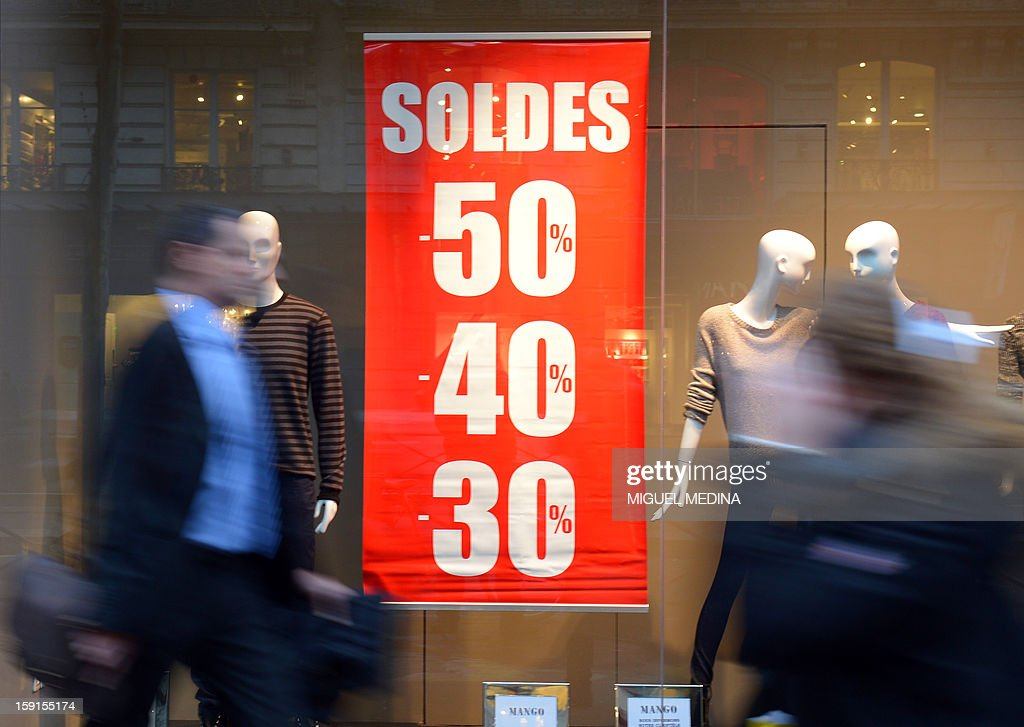 A man passes by advertising signs for winter sales in Paris, on January 9, 2013.