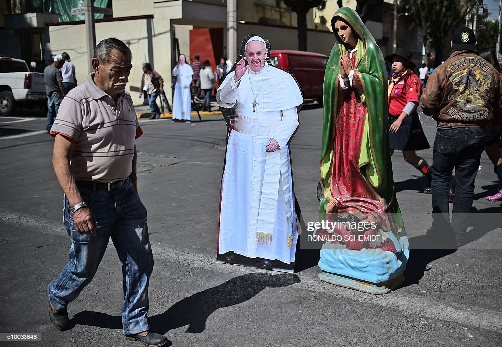 A man passes by an image of the Holy Virgin and another depicting Pope Francis in the vicinity of the Guadalupe Basilica in Mexico City on February 13, 2016. Francis will be the first pope to enter Mexico's National Palace to meet President Enrique Pena Nieto, as he starts a cross-country tour that will highlight the country's violence and migration troubles. AFP PHOTO / RONALDO SCHEMIDT / AFP / RONALDO SCHEMIDT