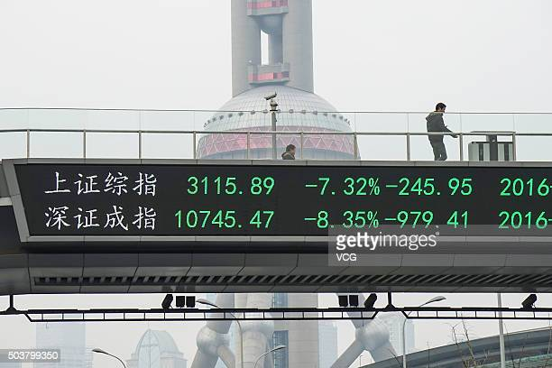 A man passes by electric screen showing Chinese shares decreases sharply to a halt point on January 7 2016 in Shanghai China Chinese shares slumped...