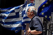 A man passes by Greek and European Union flags on June 3 in Athens Greece Greek Prime Minister Alexis Tsipras is expected to be presented with the...