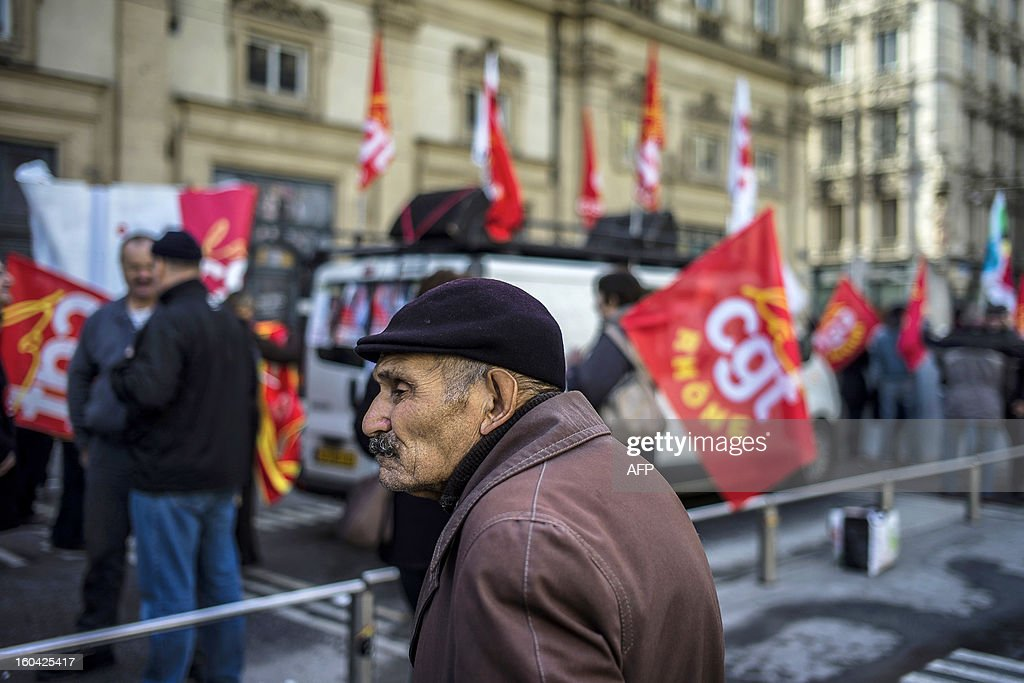 A man passes by members of the public sector, (education, health and finance) taking part on January 31, 2013 in a national day of protest in Lyon against the French government's social policy. For the first time since French President Francois Hollande's election, three labour unions (CGT, FSU, Solidaires) called on 5.2 million civil servants to stop working to show to the government their unhappiness, particularly in terms of purchasing power.
