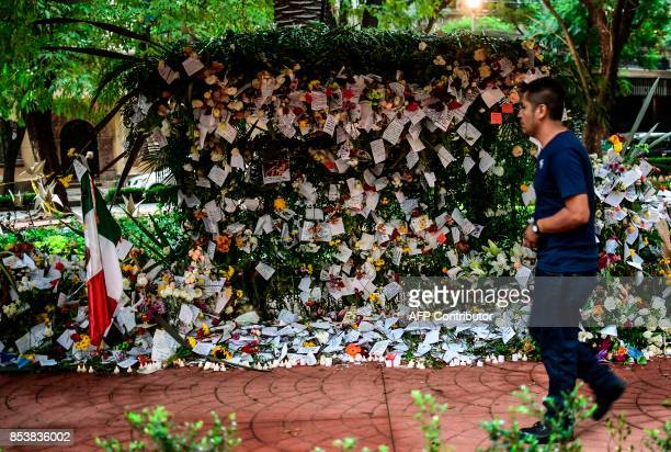 TOPSHOT A man passes by messages placed in an offering to the victims of Mexico City's earthquake on September 25 2017 Hopes of finding more...