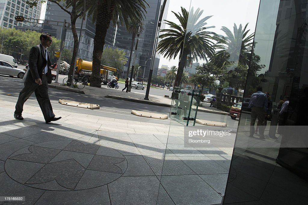 A man passes by the entrance of Bolsa Mexicana de Valores (BMV), Mexico's stock exchange, in Mexico City, Mexico, on Wednesday, July 31, 2013. Mexico's economy is forecast to grow 2.8 percent this year based on analyst estimates compiled by Bloomberg. Photographer: Susana Gonzalez/Bloomberg via Getty Images
