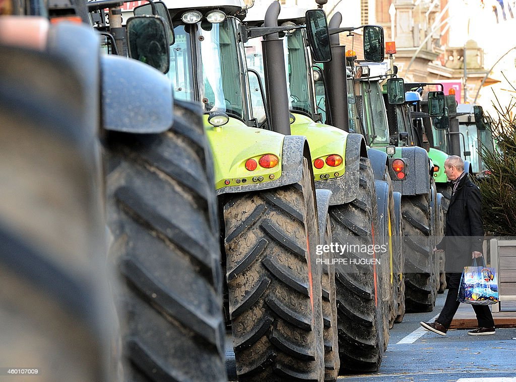 A man (R) passes by tractors blocking the road on January 2, 2014 in Dunkerque, northern France, during a demonstration by farmers called by the Gers farmers' union FDSEA to protest against the regional and ecological key measure of the Grenelle Environment, known as 'La Trame verte et bleue' (blue-green infrastructure). AFP PHOTO / PHILIPPE HUGUEN