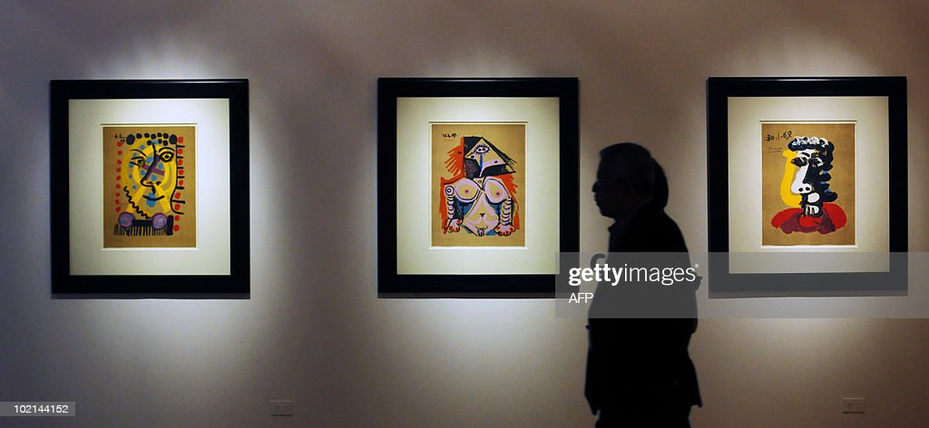 A man passes by works of the exhibition 'Imaginary Portraits' of Spanish artist Pablo Picasso, displayed in the Museum of Art in San Salvador, El Salvador on June 16, 2010, as part of a twenty-nine paintings. AFP PHOTO/ Jose CABEZAS