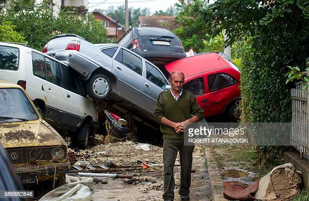 TOPSHOT A man passes damaged vehicles in the village of Stajkovci near Skopje on August 7 following overnight torrential rains and fierce storms...