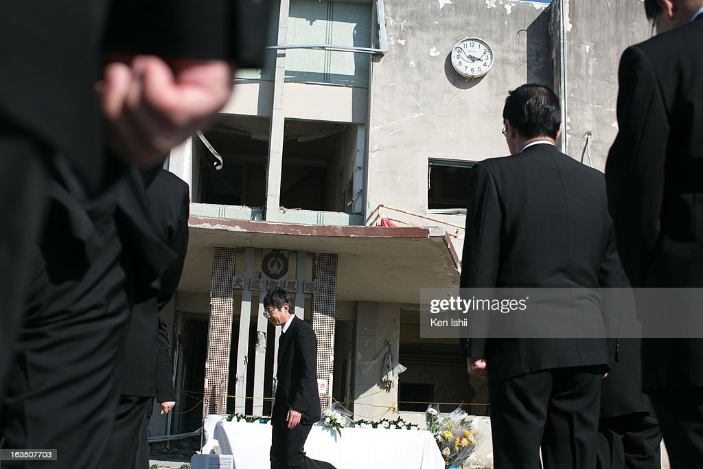 A man passes in front of a destroyed former town government office, where 33 civil servants are missing or dead on March 11, 2013 in Ootsuti, Iwate prefecture, Japan. On March 11 Japan commemorates the second anniversary of the magnitude 9.0 earthquake and tsunami that claimed more than 18,000 lives.