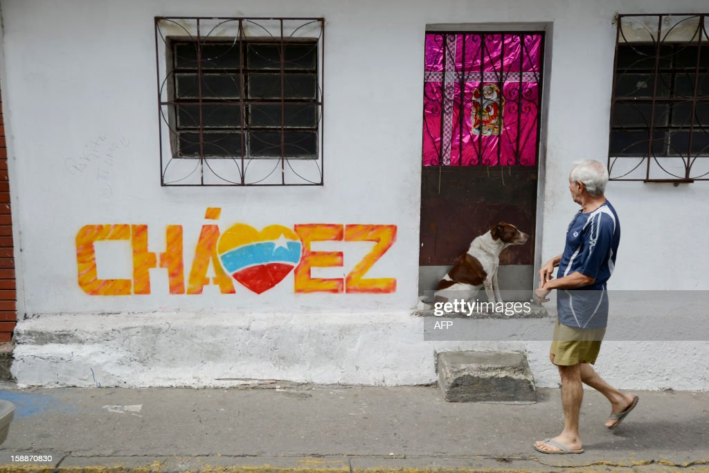 A man passes in front of a graffiti of Venezuelan President Hugo Chavez in Caracas, on January 2, 2013. Chavez is conscious and fully aware of how 'complex' his condition remains three weeks after difficult cancer surgery in Havana, the Venezuelan president's handpicked successor, Vice President Nicolas Maduro, said Tuesday. Maduro, who is returning to Caracas today on January 2, provided no specifics about Chavez's condition but defended the government's efforts to keep the public abreast of the president's health. Chavez underwent his fourth cancer-related surgery three weeks ago in Havana and has been bed-ridden ever since. AFP PHOTO/LEO RAMIREZ