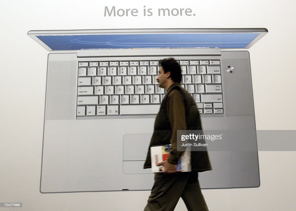 A man passes in front of a poster of the new Apple 17-inch Powerbook G4 at Macworld January 7, 2003 in San Francisco. Apple CEO Steve Jobs announced announced new 17-inch and 12-inch powerbooks as well as several new software updates.