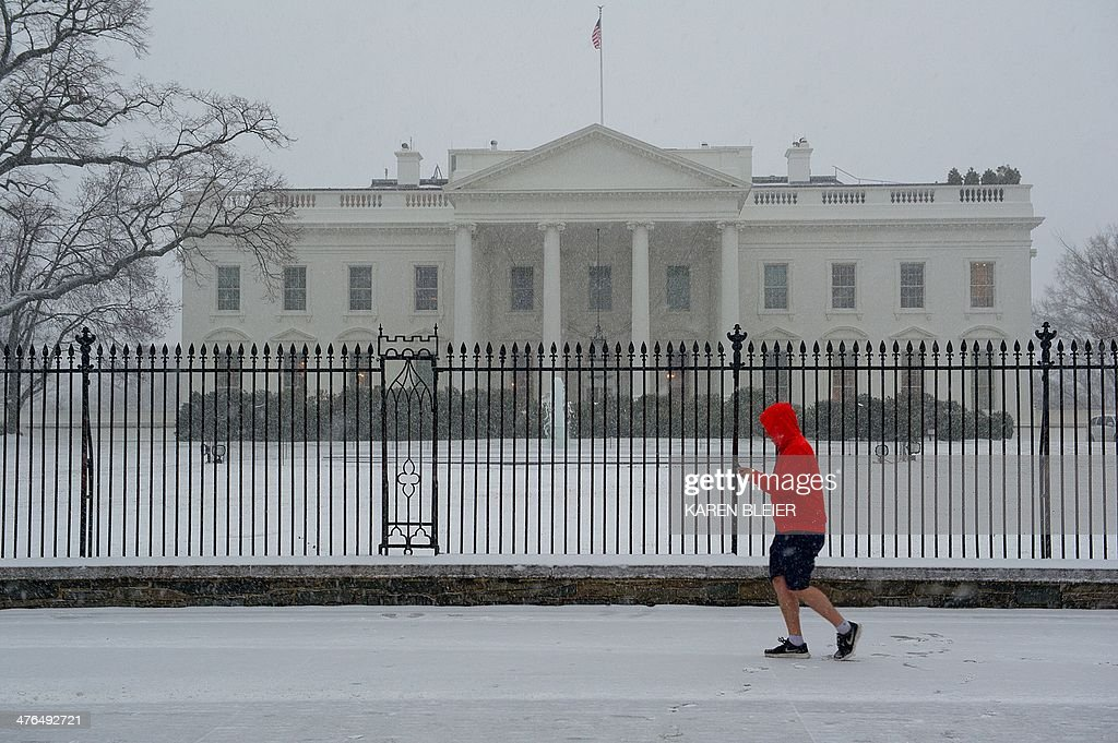 A man passes in front of the White House during a snow strom March 3, 2014 in Washington, DC. Snow began falling in the nation's capital early Monday, and officials warned people to stay off treacherous, icy roads a scene that has become familiar to residents in the Midwest, East and even Deep South this year. Schools were canceled, bus service was halted in places and federal government workers in the DC area were told to stay home Monday. AFP PHOTO / Karen BLEIER