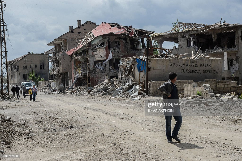 A man passes rubble of damaged buildings following heavy fightings between government troops and Kurdish fighters after the curfew on May 30, 2016 in the majority Kurdish city town of Yuksekova, southeastern Turkey near the border with Iraq and Iran. / AFP / ILYAS