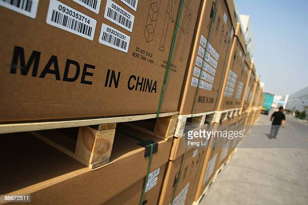A man passes the photoelectric board products cased at the plant of Tianwei Yingli Green Energy Resources Co Ltd on June 24 2009 in Baoding China...