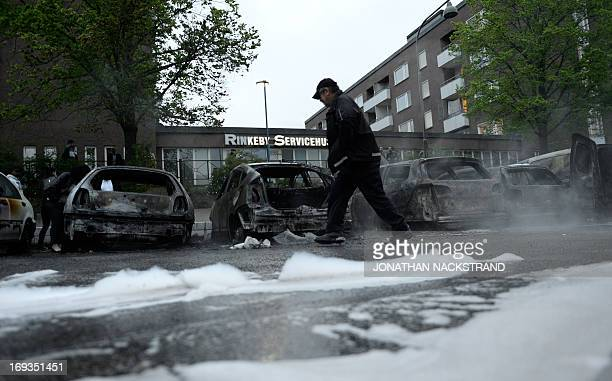 A man passes the scene of cars gutted by fire in the Stockholm suburb of Rinkeby after youths rioted in several different suburbs around Stockholm...