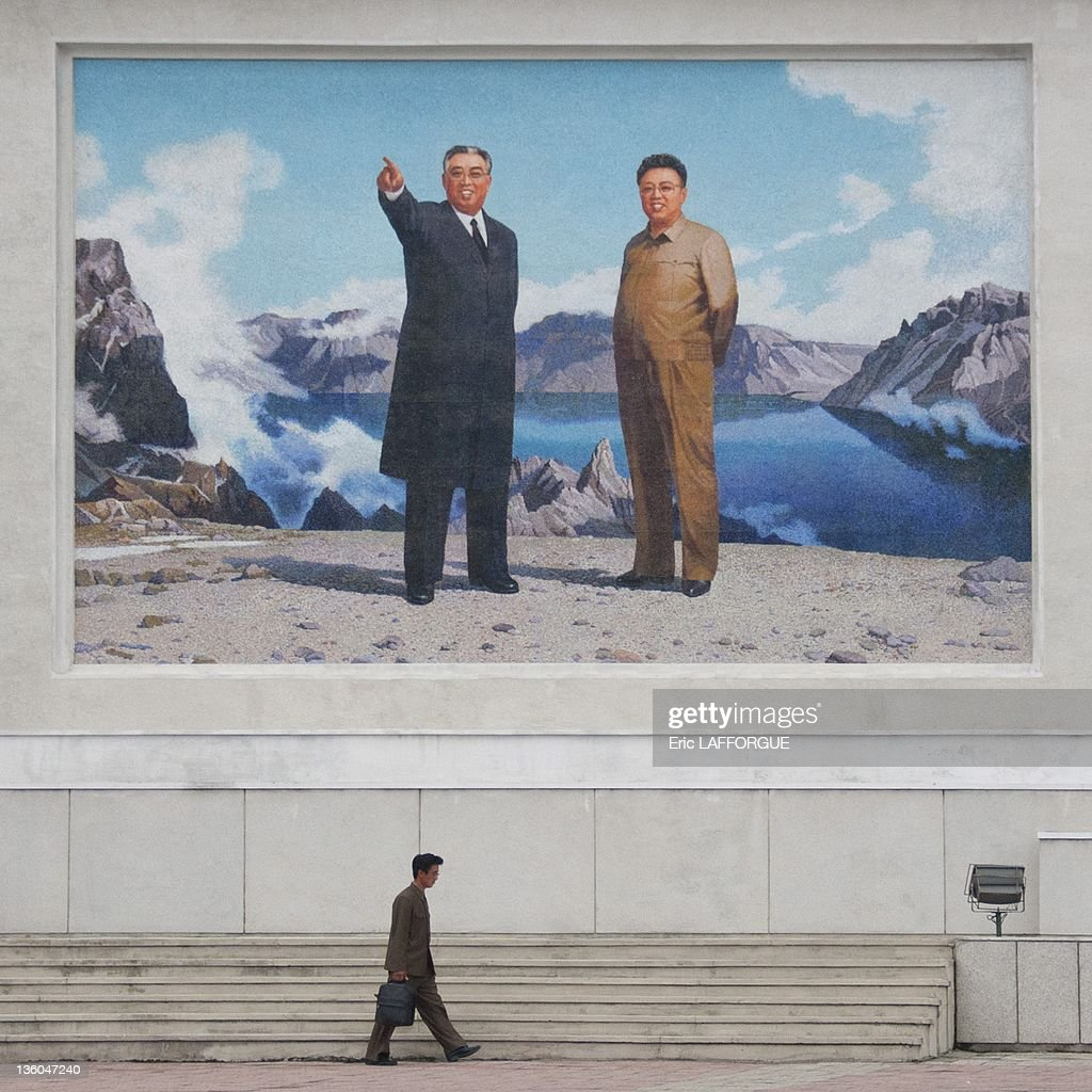 A man passes underneath a giant poster of leaders Kim Il Sung and Kim Jong Il on September 14, 2011 in Wonsan, North Korea.