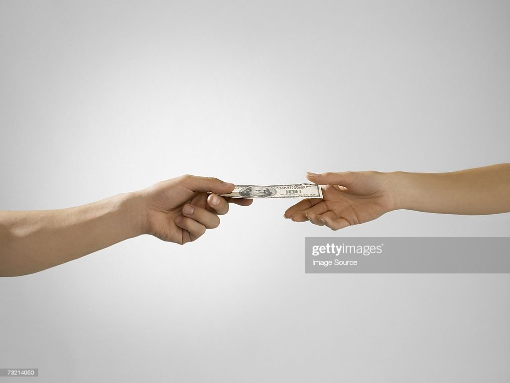Man passing banknote to woman : Stock Photo