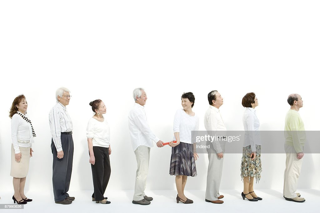 Man passing baton to woman in a row