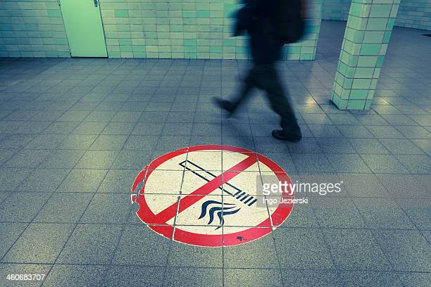 Man passing by non-smoking sign on floor