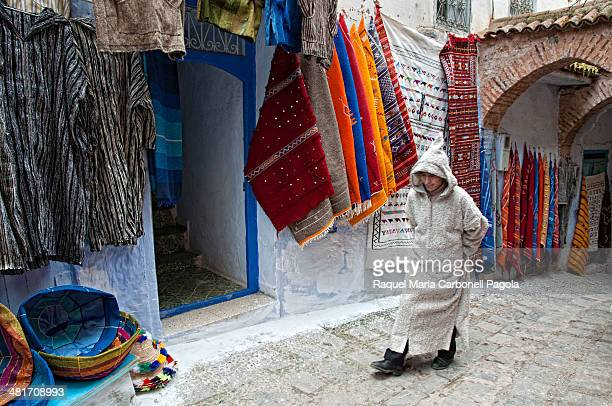Man passing by textile shops in the medina