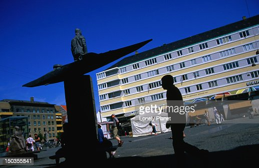 Man passing Inuit sculpture on Christianshavn Torv. : Photo
