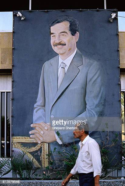 Man Passing Painting of Saddam Hussein in Suit