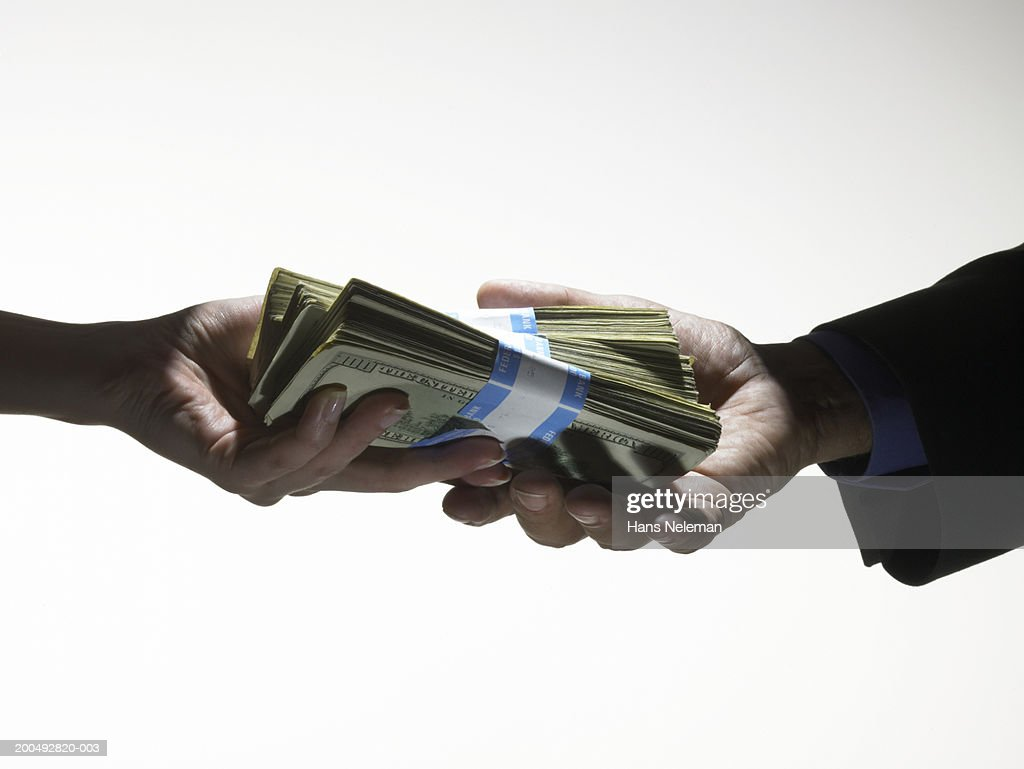 Man passing woman large wad of banknotes, close-up, side view : Stock Photo