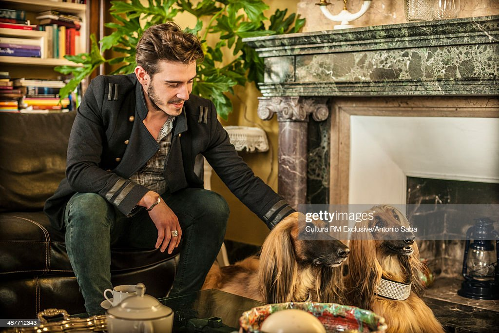 Man patting dog by fireplace : Stock Photo