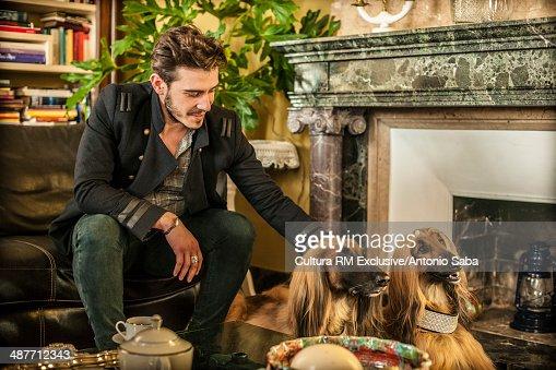 Man patting dog by fireplace : Stock Photo