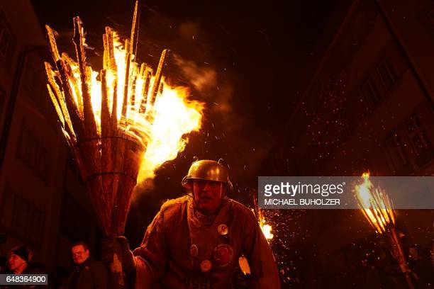 A man pauses as he carries burning bundles of pinewood chips on his shoulders during the 'Chienbase' procession on March 5 2017 in Liestal northern...
