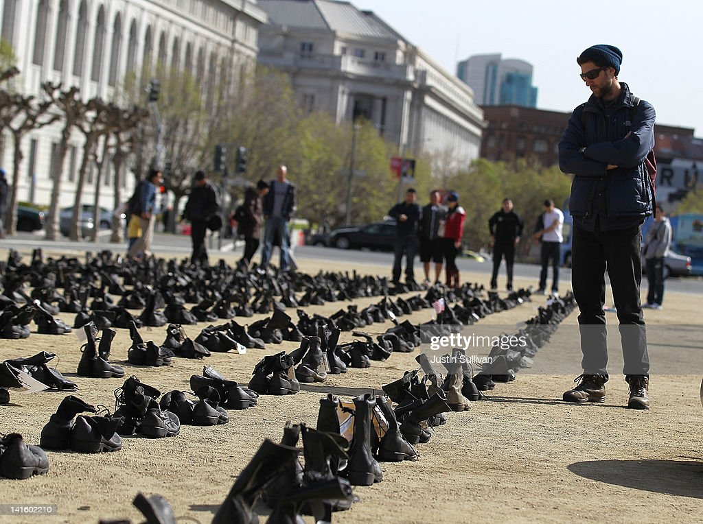 A man pauses as he looks at rows of combat boots that are part of the 'Eyes Wide Open' exhibit in front of San Francisco City Hall on March 19, 2012 in San Francisco, California. The Eyes Wide Open exhibition includes a pair of boots for every one of the 481 California servicemen and women who died in the Iraq war.
