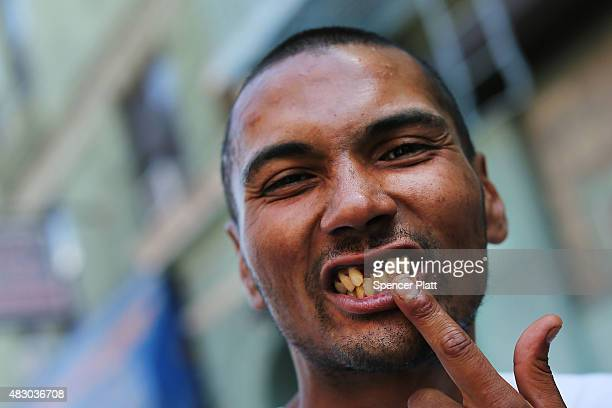 A man pauses as he smokes K2 or 'Spice' a synthetic marijuana drug along a street in East Harlem on August 5 2015 in New York City New York along...