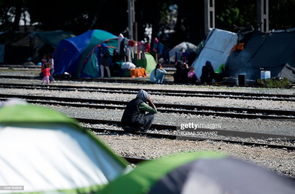 A man pauses at rail tracks at a makeshift camp for migrants and refugees near the village of Idomeni not far from the Greek-Macedonian border on May 1, 2016. Some 54,000 people, many of them fleeing the war in Syria, have been stranded on Greek territory since the closure of the migrant route through the Balkans in February. / AFP / TOBIAS
