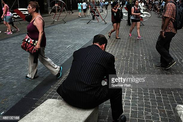 A man pauses by the New York Stock Exchange on August 24 2015 in New York City As the global economy continues to react from events in China markets...