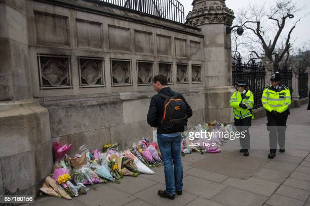 A man pauses in front of floral tributes laid outside the Houses of Parliament as police officers patrol following Wednesday's attack on Westminster...