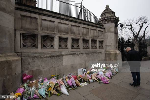 A man pauses in front of floral tributes laid outside the the Houses of Parliament following Wednesday's attack on Westminster on March 24 2017 in...