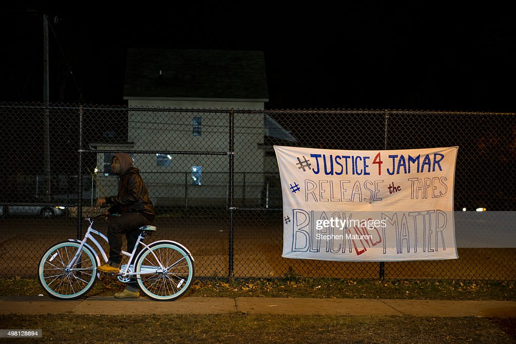 A man pauses on his bike while passing through the protests outside the 4th Precinct police station November 20 2015 in Minneapolis Minnesota...