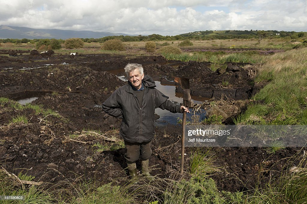 A man pauses while cutting turf in a peat bog in southwest Ireland.