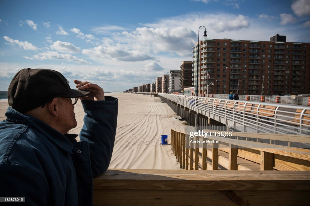 A man pauses while walking down the Long Beach boardwalk on October 25, 2013 in Long Beach, New York. The Long Beach boardwalk was severely damaged by Superstorm Sandy last year, which killed 285 people and caused billions of dollars in damage, though the boardwalk reopened today. Long Beach's new boardwalk is made of Brazilian hardwood and is estimated to have a lifespan of 30-40 year; the previous boardwalk was only scheduled to last three to seven years.
