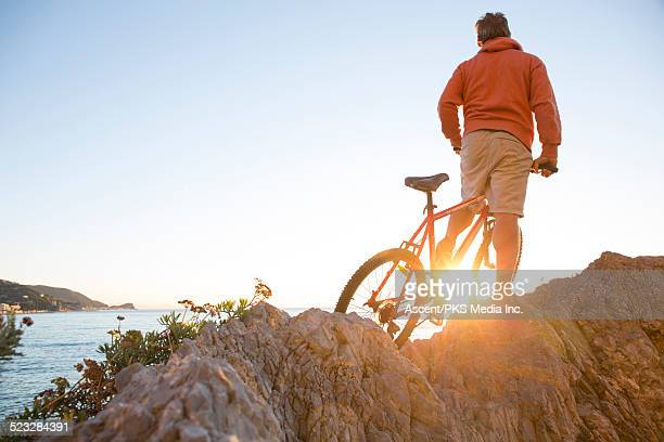 Man pauses with bicycle above sea, sunrise