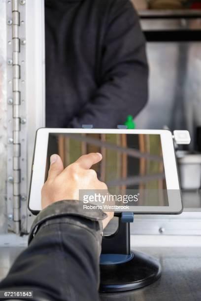 Man paying at food cart using digital tablet