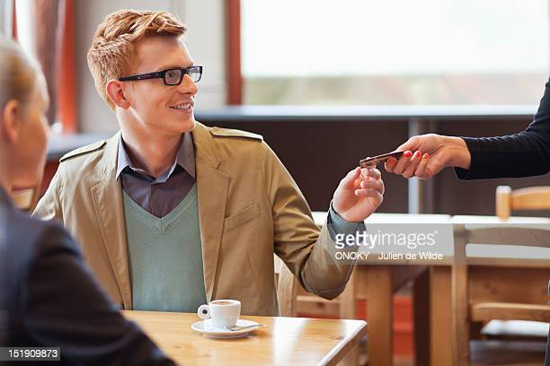 Man paying bill by credit card in a restaurant