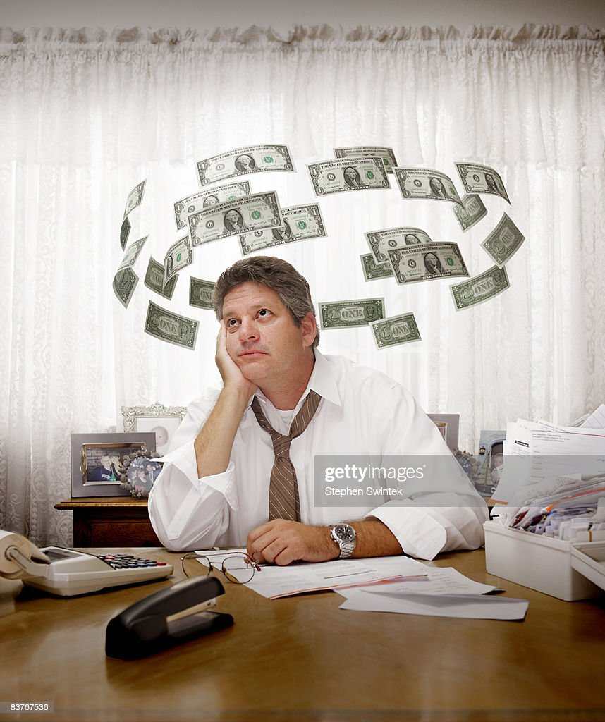 Man paying bills surrounded by flying dollars : Stock Photo