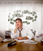 Man paying bills surrounded by flying dollars