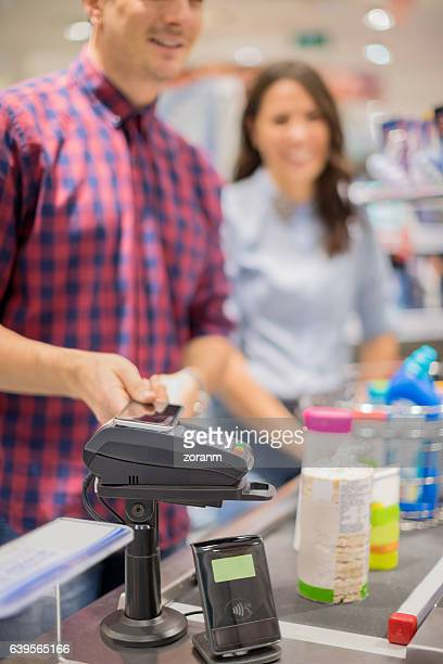 Man paying contacless in supermarket